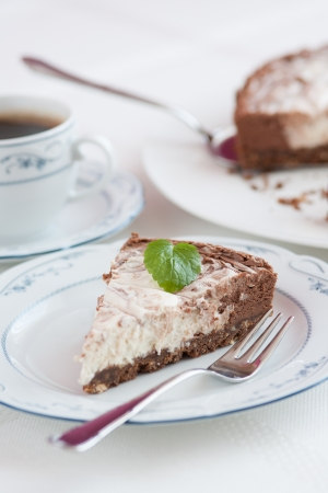 Beautiful chocolate-raw cheese cake ready to eat with cup of coffee, main focus on mint leaf  photo
