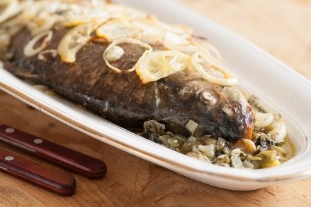 Oven baked carp fish with onions and lemon