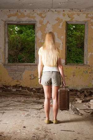 Young woman standing with vintage suitcase in abandoned building