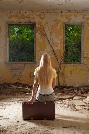 woman back: Young woman sitting on vintage suitcase in abandoned building Stock Photo