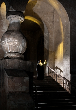 vestal: Nun on stairs of nunnery holding candle lamp