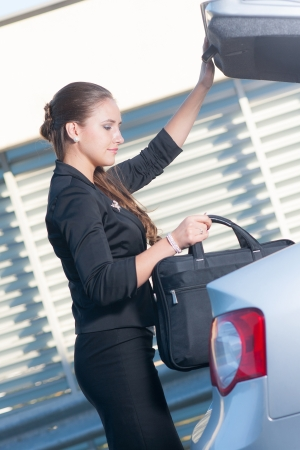 Businesswoman takes her laptop bag out from the car Banque d'images