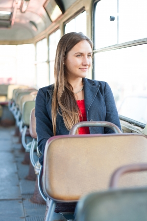 Beautiful young woman sitting in vintage bus photo
