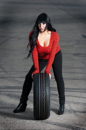 Attractive woman and car tire Stock Photo - 25062013