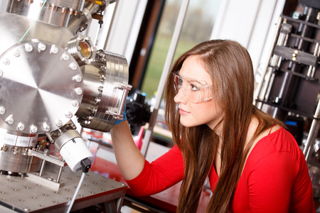 Female scientist looking to the laser deposition chamber