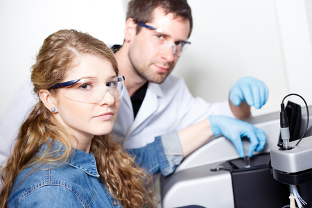 conducting: scientists conducting research in a lab environment