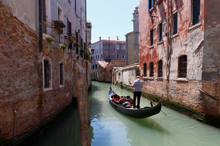 gondolier: Venetian gondolier punting gondola through canal waters of Venice Italy Stock Photo