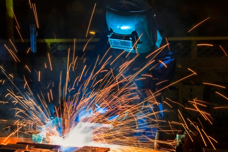 Welders team welding automotive part at assembly line in car factory