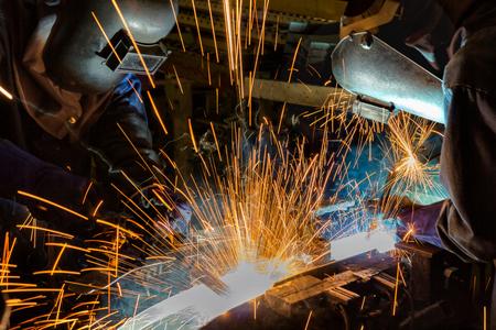 Welders team welding automotive part in assembly line