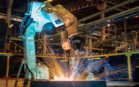 Auto robot is welding assembly metal part in factory
