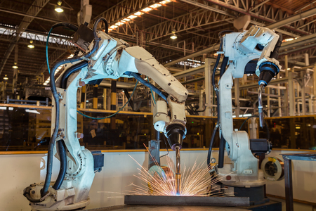 산업용 로봇은 자동차 조립 공장에서 새로운 프로그램을 실행합니다. 스톡 콘텐츠