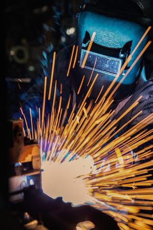 Worker is welding steel part in factory Stock Photo