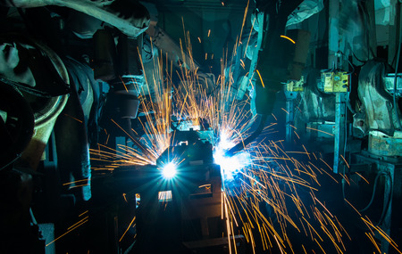 Industrial welding robots in production line manufacturer factory Stock Photo