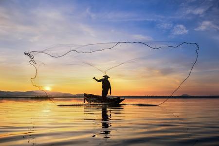 Rybak sylwetka na łodzi rybackiej z zmierzchem