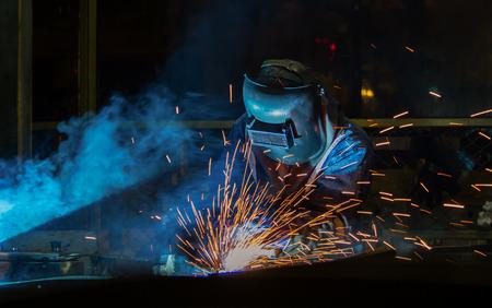 Industrial worker is welding metal part in factory