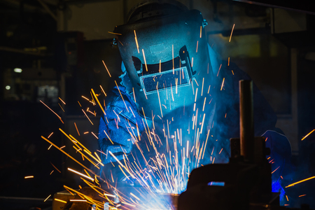 Industrial worker is welding in factory Stock Photo