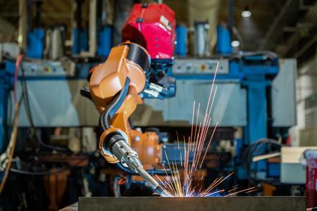 공장에서 자동차 부품을 용접하는 산업용 로봇