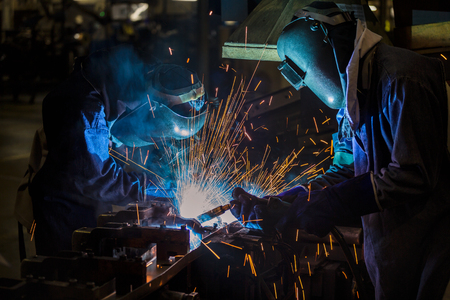 Team workers are welding part in factory