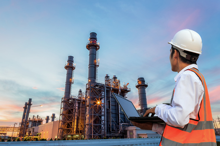 Engineering is use notebook check and standing in front of oil refinery building structure in heavy petrochemical industry