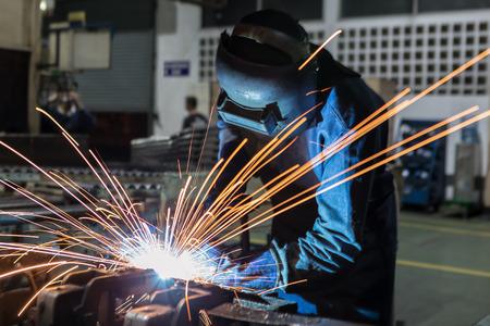 Trabajador industrial en la fábrica está soldando piezas de automóviles Foto de archivo