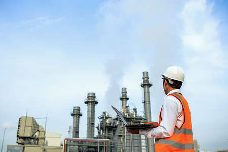Engineering is working in gas turbine electric power plant he check around plant with notebook