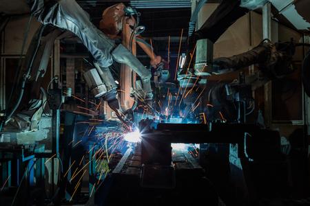 Team industrial robots are welding in factory