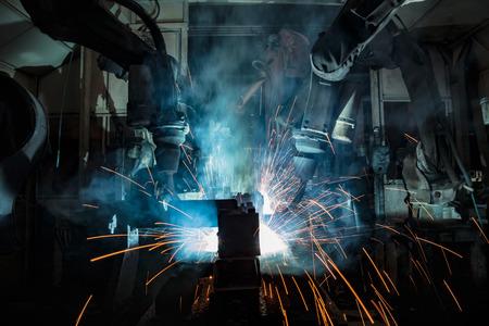 Industrial robots are welding in factory Imagens