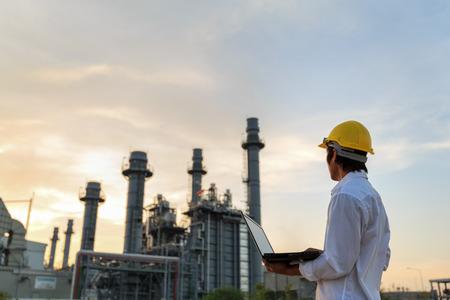 Engineer use laptop check gas turbine electric power plant