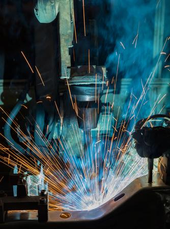 Closeup robot welding in car factory