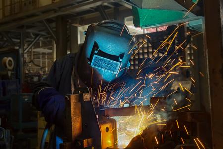 worker is welding repair automotive part in car factory