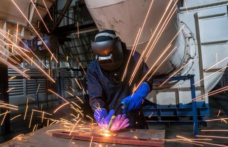 Worker is welding automotive part in car factory
