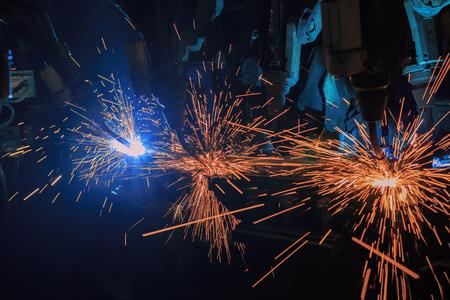 Team robot welding automotive part in factory Фото со стока