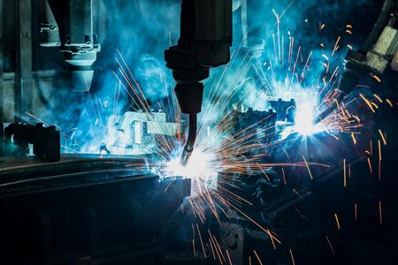 Closeup industrial robots are welding in factory