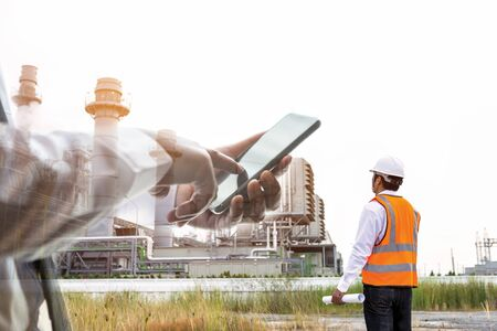 Engineering and businessman are checking around gas turbine electricity power plant with smart phone
