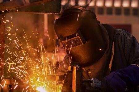 Worker is welding in car factory