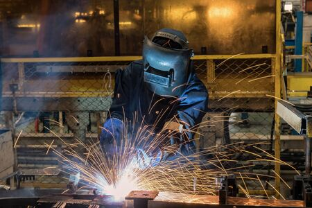 welderis welding assembly car parts in factory with protection mask