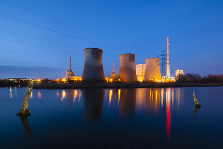 A coal-fired power station in river landscape with dead trees at night Standard-Bild