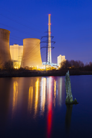 coal fired: A coal-fired power station in river landscape with dead tree at night Stock Photo