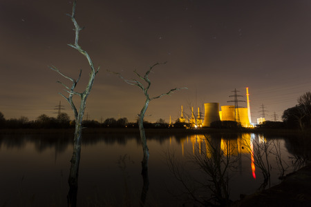coal fired: A coal-fired power station in river landscape with dead trees at night Stock Photo