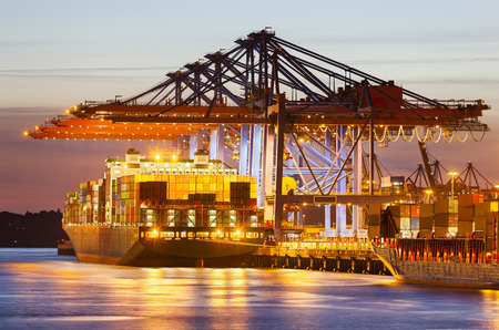 ports: Container ship at a terminal at dusk Stock Photo