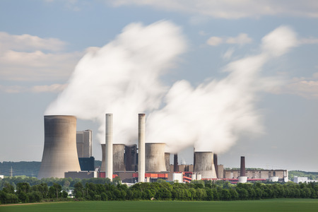 Long exposure shot of a coal-fired power station in the distance in agricultural landscape. The power station Niederaussem has the second highest cooling tower in the world with a height of 200m.