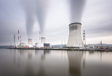 nuclear power station: Long exposure shot of a large nuclear power station by a river on a gray day Stock Photo