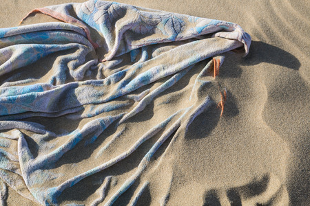 A beach towel covered by flying sand at Playas de Sotavento, Fuerteventura