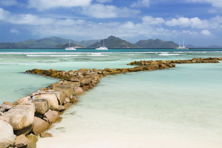 Perfect white beach in La Digue, Seychelles protected by a row of boulders leading into the image, some boats in the background Stock Photo