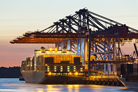 Container ship at a terminal at dusk Foto de archivo