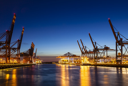 A large container harbor with deep blue night sky