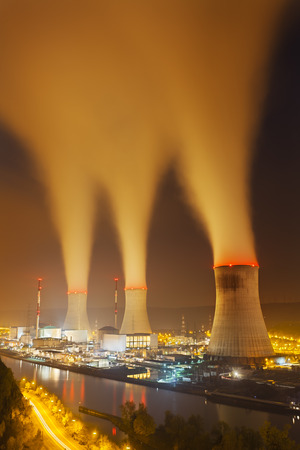nuclear power station: A large nuclear power station by a river at night with lots of steam Stock Photo