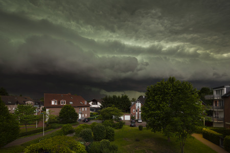 upcoming: Spectacular cloud front of an upcoming thunderstorm turning day into night. The thunderstorm was one of the worst of the last decade in the west of Germany and caused heavy damage. Stock Photo