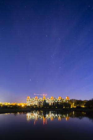 대학 병원 (Uniklinik) 밤에 작은 호수에서 반사와 위의 오리온 별자리가있는 별이있는 아헨. 스톡 콘텐츠