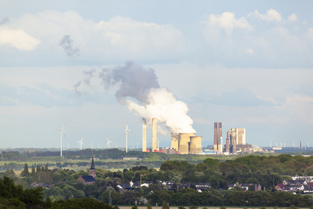View from a slag heap over rural landscape to a distant steaming coal-fired power station surrounded by wind turbines. photo